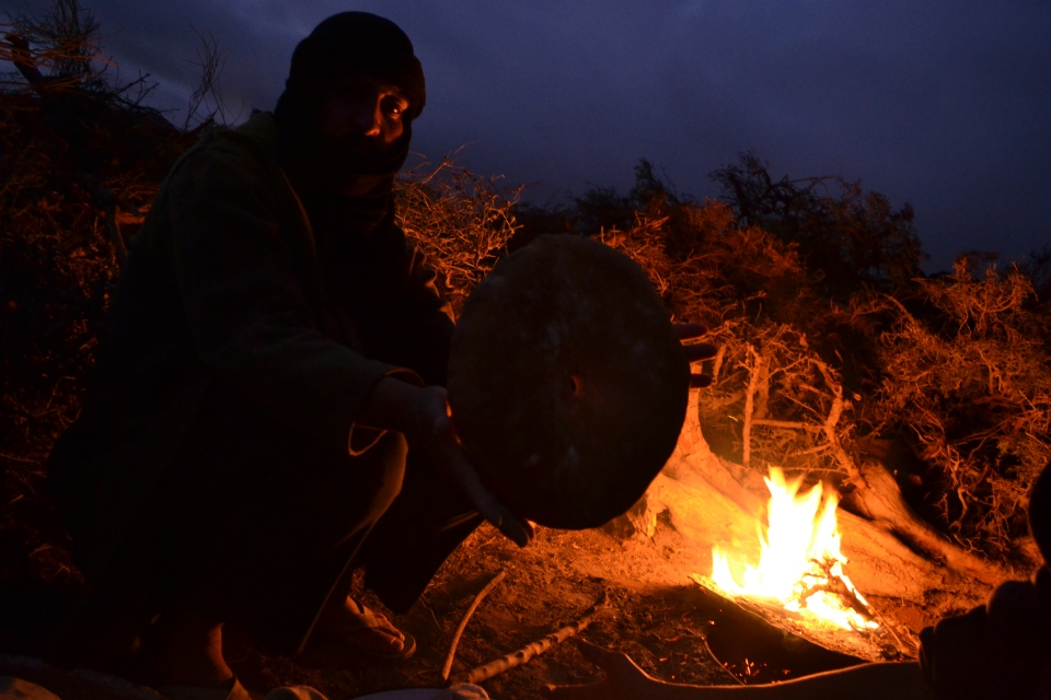 Amazigh nomad in southern Morocco baking bread in an underground oven. The dough is put in a round container submerged in the sand, then a lid is placed on top. This man used an old oil drum. Imazighen pile tinder on the lid, and burn it to bake the bread below. This process is usually the domain of women in Amazigh society. However, none of the women of this family wanted to be photographed, so this man volunteered himself for the shot. Apparently, his bread wasn't quite as good as his daughter's.