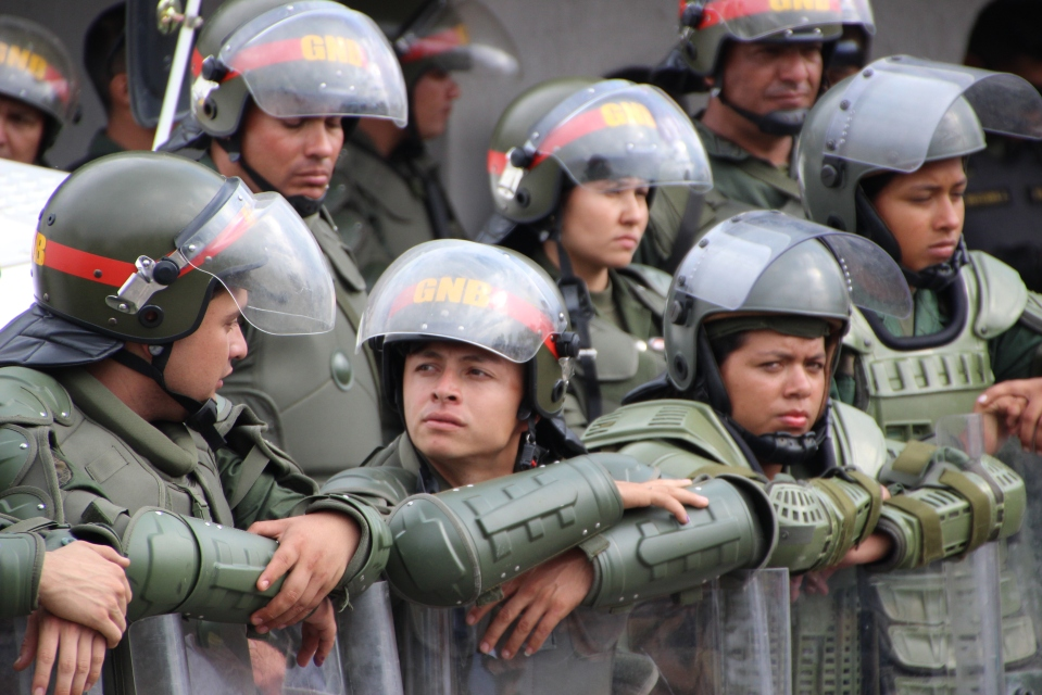 Soldiers guarding a the Merida offices of Venezuela's electoral commission following the 14 April elections. Most of these troops were only armed with riot shields, while opposition supporters protesting the election results rallied outside the offices. Many of the protesters brought Molotov cocktails, knives, baseball bats and other weapons. Minutes after this photograph was taken, opposition protesters clashed with Chavistas, who had gathered to hold a rally of their own a few hundred metres down the road. Some of the Chavistas were similarly armed, but poorly equipped police broke up the violence without appearing to harm anyone themselves. Protesters soon moved to side streets, where they repeatedly clashed out of sight from authorities. In the international media, these opposition protests were generally depicted as peaceful rallies being crushed by government forces. The reality on the ground was a little more complicated.